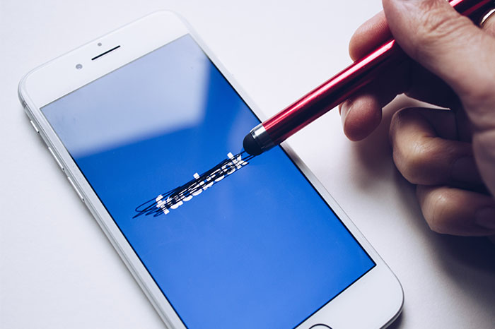 Crossing out the Facebook logo on a cell phone